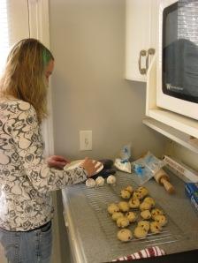 rolling pecan cookies in powdered sugar